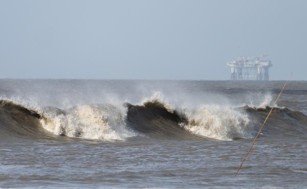 Hurricane Laura sends large waves crashing on a beach in Cameron, La., on Aug. 26 as an offshore oil rig appears in the distance. The most active hurricane season on record was just one of many challenges facing the oil industry this year — aside from t