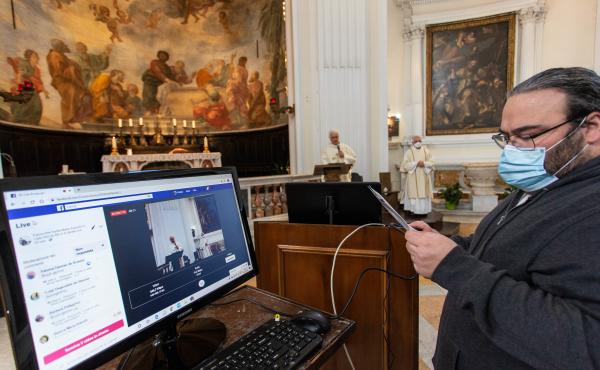 A technician sets up a livestream in Rome's empty Santa Maria Assunta in Cielo church on Sunday. Italy's prime minister has announced a gradual ending of restrictions in the hard-hit country.