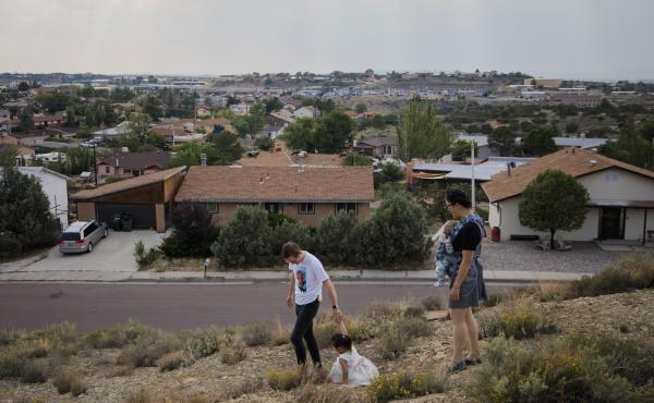Dr. Chris Hoover (left) and Dr. Connie Liu (right) walk through their home with their children Taro, 3, and Hiro, 4 months, in Gallup, N.M. On a short reporting trip across the Southwest, NPR met very different families and asked them the same simple ques