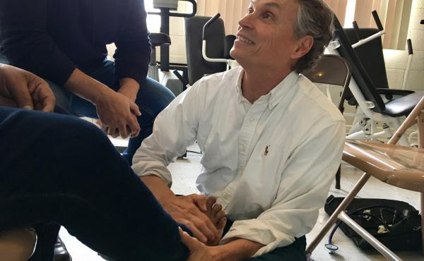 Dr. Bert Johansson, an El Paso pediatrician, treats lesions on a migrant man's foot at a makeshift clinic within a local shelter.