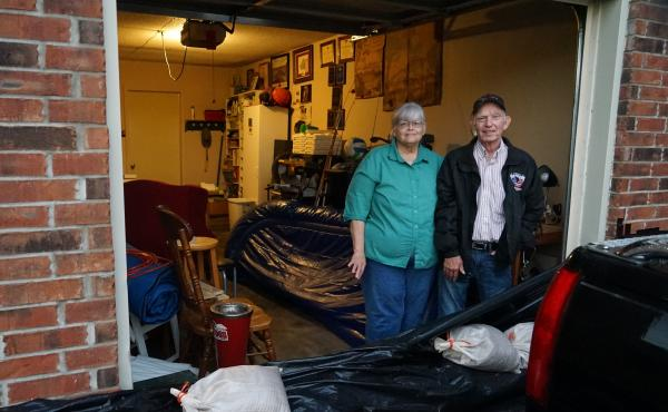 John and Louise Hutchins stand in their garage in Fort Smith, Ark., behind a homemade sandbag barrier. They chose not to evacuate, in part because they did not think their neighborhood would flood.