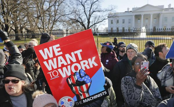 Union members and other federal employees protest in front of the White House on Thursday. Many are out of work as the partial government shutdown has dragged on longer than any in history.