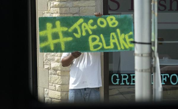 A Jacob Blake sign was on display as the motorcade of then-presidential candidate Joe Biden passed by in Kenosha Wis., on Sept. 3, 2020. A team of attorneys representing Blake have filed an excessive force lawsuit against the officer who shot and paralyze