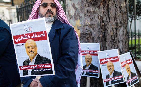 Jamal Khashoggi's fiancee and others will speak about his life and legacy on Friday, one month after he was killed in Saudi Arabia's consulate in Istanbul. Here, a protester holds a placard showing solidarity for Khashoggi during a demonstration outside t