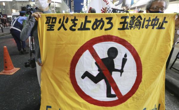 """People carry a banner reading """"Extinguish the Olympic torch"""" during a march in Tokyo last week calling for the cancellation of the Summer Olympics. The government insists the games will go on despite concerns about the coronavirus."""