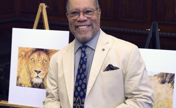 Children's book illustrator Jerry Pinkney poses in front of two of his illustrations in 2016, at the City Hall in Philadelphia.