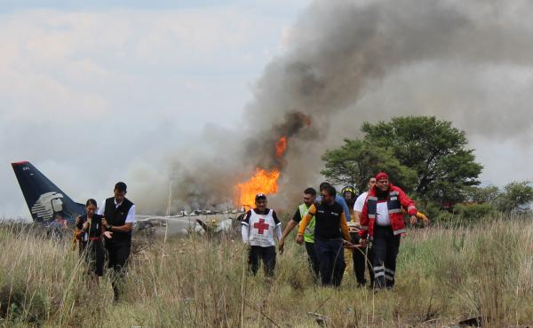 Red Cross workers and rescue workers carry an injured person on a stretcher as airline workers walk away from the site where an Aeromexico airliner crashed in a field near the airport in Durango, Mexico, on Tuesday.