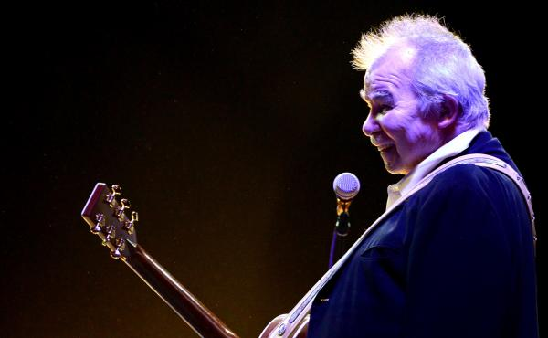 John Prine, seen here performing during Coachella in 2014, died Tuesday night from complications of COVID-19.
