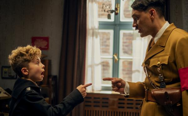 JoJo Rabbit follows a young German boy (Roman Griffin Davis, left) growing up in the Third Reich with his imaginary friend, Adolf Hitler (Taika Waititi, right).