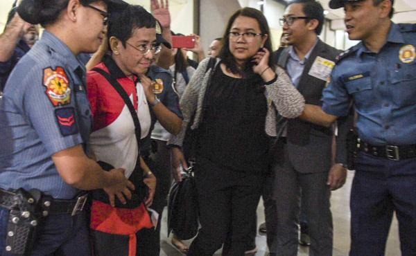 In this photo released by Rappler, CEO and Executive Editor Maria Ressa, second from left, is escorted by police after being arrested upon her arrival at Manila's International Airport on Friday.