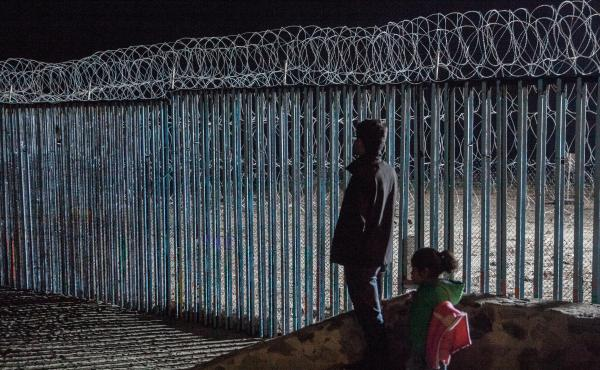 A young man and a little girl look at the border fence from Playas de Tijuana, Mexico. Photojournalist Ariana Drehsler has been covering the caravan of migrants for weeks. In December, Customs and Border Protection agents began pulling her over for questi