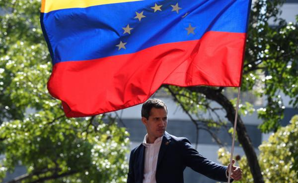 Venezuelan opposition leader and self-proclaimed acting president Juan Guaido stands under the national flag during a gathering with supporters after members of the Bolivarian National Guard joined his campaign to oust President Nicolas Maduro, in Caracas