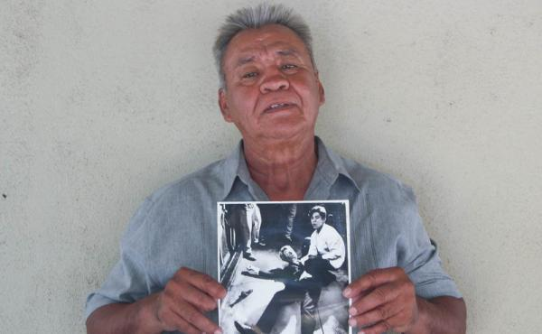Juan Romero earlier this year at his home in Modesto, Calif., holding a photo of himself and Sen. Robert F. Kennedy, taken by The Los Angeles Times' Boris Yaro on June 5, 1968. Romero died this week at age 68.