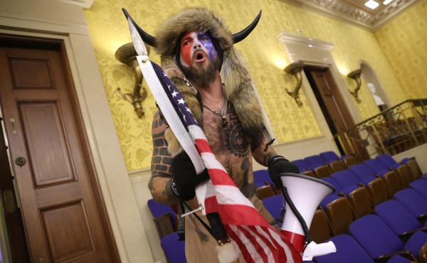 """Jacob Chansley, photographed during the Jan. 6 U.S. Capitol insurrection, screams """"Freedom"""" inside the Senate chamber following the breach of a mob during a joint session of Congress."""