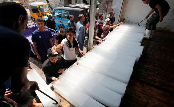 Iraqis buy ice blocks at a factory in Sadr City, east of the capital, Baghdad, on July 2 amid power outages and soaring temperatures.