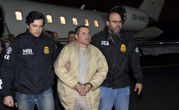"""U.S. law enforcement personnel escort Joaquín """"El Chapo"""" Guzmán from a plane to a waiting caravan of SUVs at New York's Long Island MacArthur Airport in January 2017."""