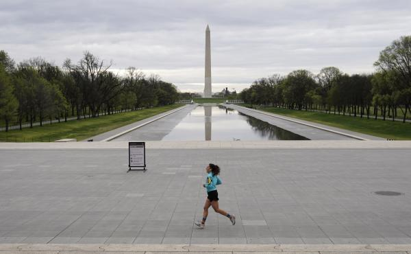 A woman jogs along a mostly empty National Mall on March 31, 2020 in Washington, D.C. To prevent the spread of the coronavirus, Virginia, Maryland and the District of Columbia all announced stay-at-home orders this week, which strongly discourage resident