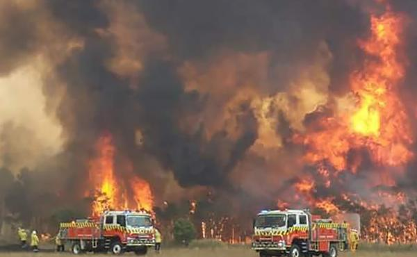 Wildfires burning across Australia's two most-populous states Tuesday trapped residents of a seaside town in apocalyptic conditions, destroyed properties and caused fatalities.