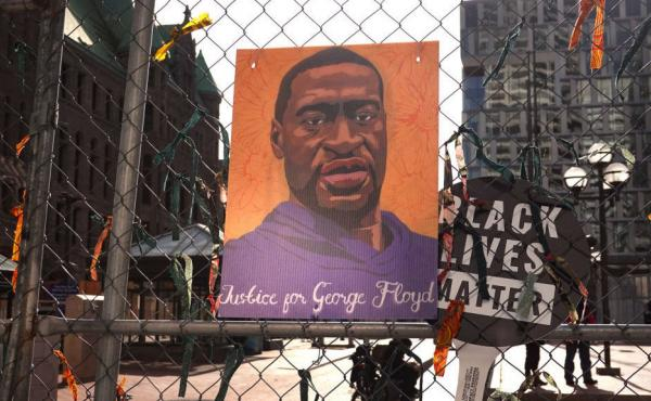 A picture of George Floyd hangs on a fence barrier that surrounds the Hennepin County Government Center in Minneapolis during the trial of former police officer Derek Chauvin in March. The Justice Department is now bringing criminal charges against Chauvi