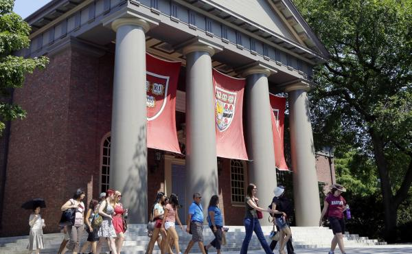 A tour group in 2012 walks through the campus of Harvard University in Cambridge, Mass.
