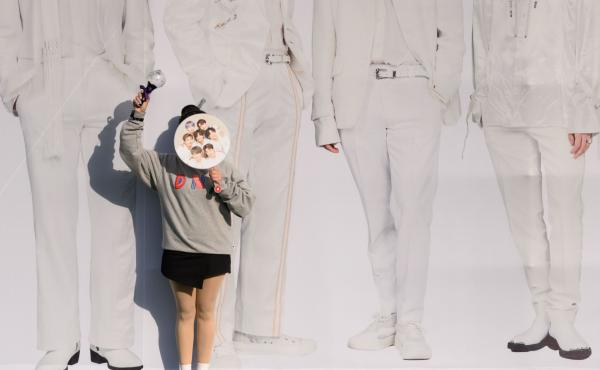 A fan of K-pop band BTS poses for photos against a backdrop featuring an image of the group's members in Seoul, South Korea, on Oct. 29, 2019.