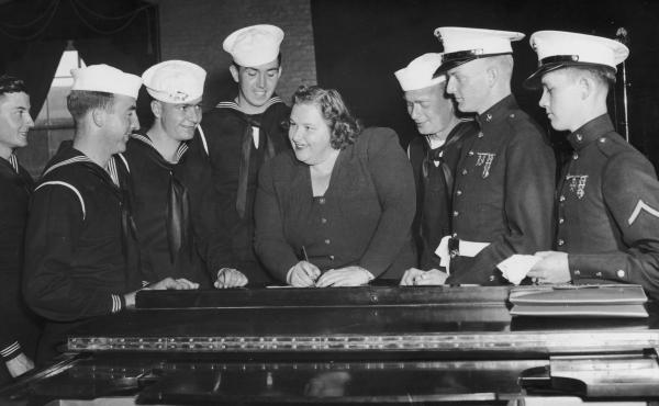 Singer Kate Smith, signing autographs for a group of American sailors c. 1938.