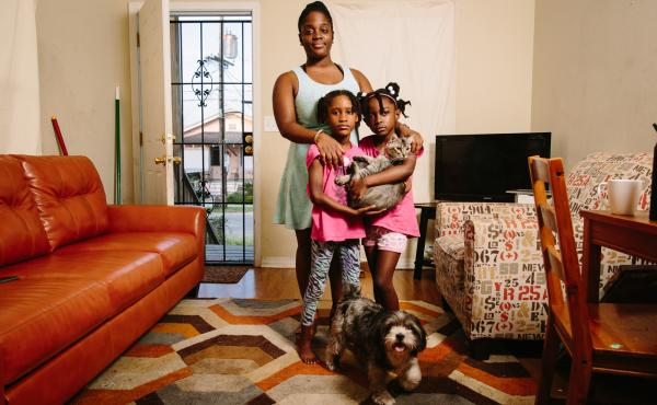 Dyha Gresham (front, left), her older sister Briceshanay (in back) and Briceshanay's daughter Uri stand in their New Orleans home with the family's cat Sugar-Pepper and dog Selena. After Katrina, Briceshanay says, she relied on theater and the arts to hel