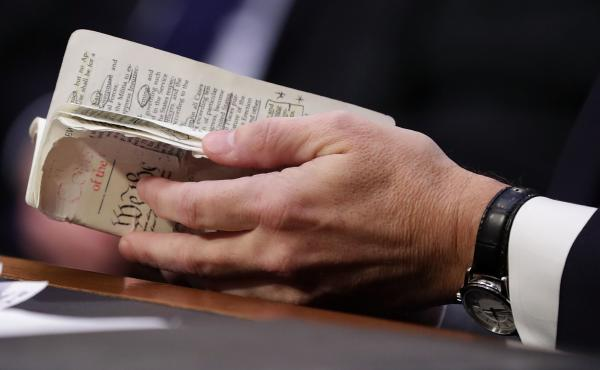 Supreme Court nominee Judge Brett Kavanaugh thumbs through a well-worn, pocket-sized copy of the U.S. Constitution as he testifies before the Senate Judiciary Committee on the second day of his confirmation hearings Wednesday.