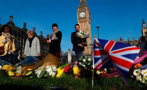 People lay floral tributes to the victims of the March 22 terror attack in Parliament Square outside the Houses of Parliament in central London.