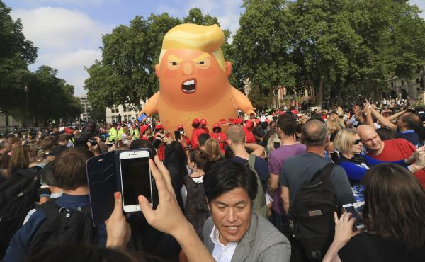 "A protest against President Trump in London's Parliament Square includes a giant balloon of ""Trump Baby"" in a diaper on Friday. It flew high above the statutes of prominent historical figures including Winston Churchill, Mahatma Gandhi and Millicent Fawce"