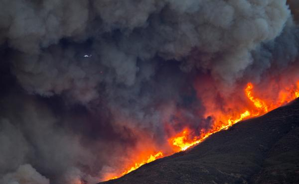 A firefighting helicopter is dwarfed by smoke and flames during Thomas Fire on Thursday.