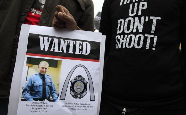 Demonstrators hold a sign in St. Louis, Mo., following the 2014 shooting death of 18-year-old Michael Brown.
