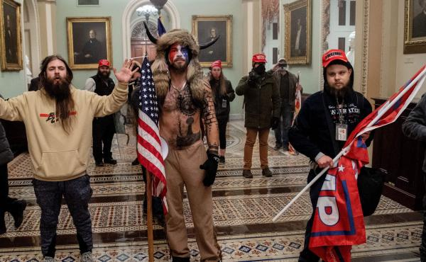 Supporters of President Donald Trump, including Jake Angeli (center), a QAnon supporter known for his painted face and horned hat, standing inside the U.S. Capitol on Jan. 6, 2021. Demonstrators breeched security and entered the Capitol as Congress debate