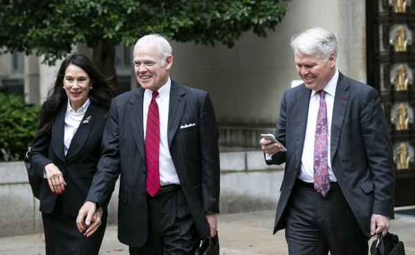 Attorney Charles Cooper, representing former national security aide Charles Kupperman (center) departs federal court in Washington in October. On Tuesday, Cooper asked a federal court to keep alive a lawsuit centered on a now-withdrawn subpoena filed by H