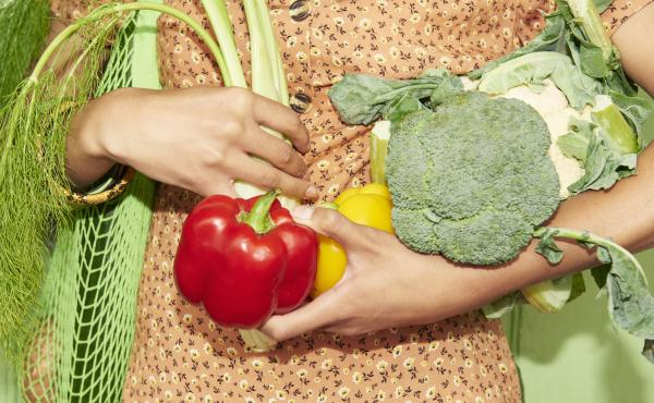 A woman wearing an orange floral, button-down dress carries a green mesh bag full of produce and holds extra produce in her arms.