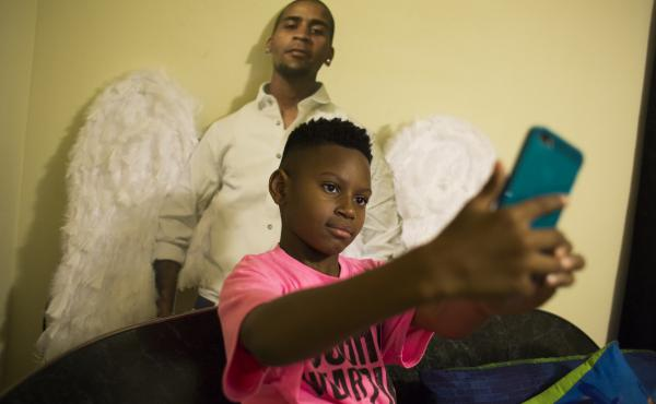 A few weeks after Javon Johnigan's shooting death on Sept. 3, 2016, his 8-year-old son Jamai demonstrates how he takes selfies with a life-size cutout of his father. Originally made for the funeral and the repast, Jamai keeps the cutout of his dad behind