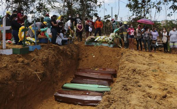 Relatives mourn at the site of a mass burial at the Nossa Senhora Aparecida cemetery, in Manaus, Amazonas state, Brazil, on Tuesday. The cemetery is carrying out burials in common graves due to the large number of deaths from COVID-19 disease, according t