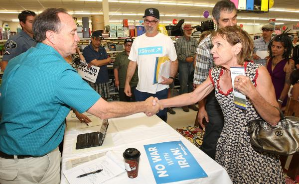 Rep. Ed Perlmutter shakes hands with Carlyn Meyer and other members of the groups J-Street and MoveOn.org as they urge him to support the Iran nuclear deal at an event in Denver. J-Street plans to spend about $5 million on ads in this fight, which is vast