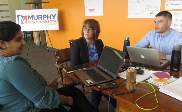 Campaign staff member Aisha Chughtai (left) speaks with Erin Murphy (center), a Democratic candidate for Minnesota governor, at the campaign's St. Paul headquarters as colleague Charles Cox looks on. Chughtai and Cox are members of a newly formed campaign