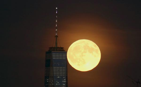 A full moon rises behind Lower Manhattan and One World Trade Center in September in New York City.