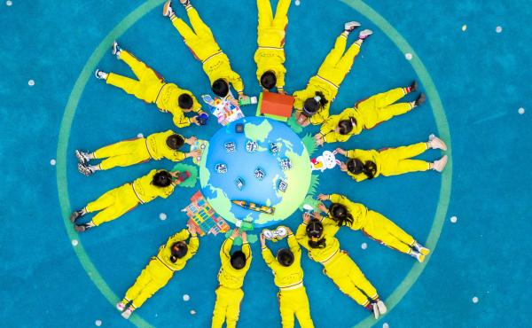 Children make an image of the Earth with green materials at a kindergarten on the 52nd Earth Day on April 22 in Changxing County, Zhejiang Province of China.