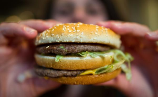 A customer holds a McDonald's Big Mac. The fast-food giant, one of the world's biggest beef buyers, has announced plans to use its might to cut back on antibiotics in its global beef supply. Environmentalists are applauding the commitment.