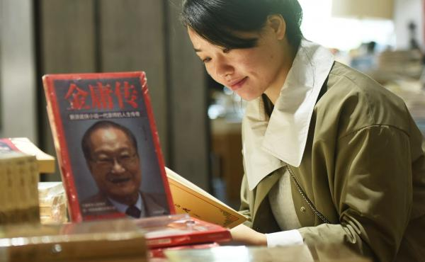 Novelist Jin Yong — the pen name for writer and journalist Louis Cha — has died, triggering tributes and mourning from his fans. Here, a customer reads a book at a memorial section at a bookstore in Hangzhou, Zhejiang Province.