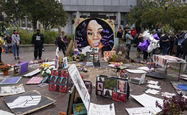 Two more Louisville police officers have been told they will be fired in the wake of the death of Breonna Taylor, whose image is seen in a memorial in September.