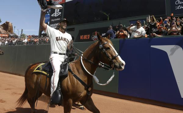 Major league pitcher Madison Bumgarner carries the 2014 San Francisco Giants championship pennant while riding a police horse before a game in 2015. The Athletic reports that Bumgarner has been competing at rodeos under an alias.