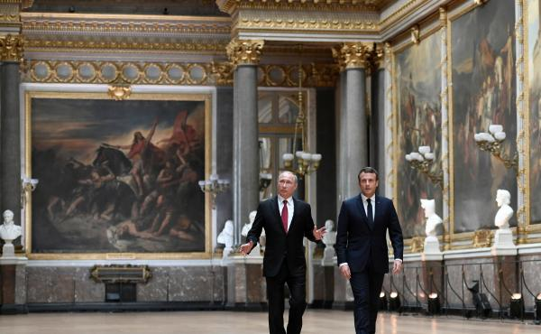 French President Emmanuel Macron (right) and Russian President Vladimir Putin walk in the Galerie des Batailles (Gallery of Battles) at the Palace of Versailles as they arrive for a joint press conference following their meeting near Paris on Monday.