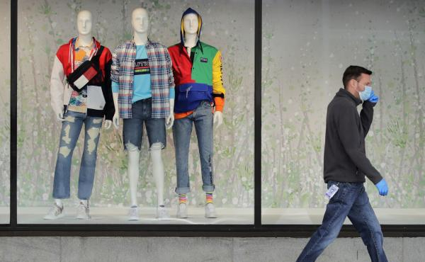 """A man walks past mannequins in the windows of a Macy's store in Boston on April 15. The company said its online sales started growing in April, but they """"only partially offset"""" the losses from its stores."""
