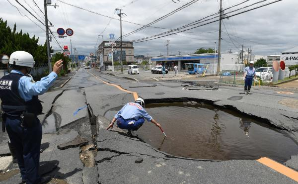 Police check a collapsed road following an earthquake in Takatsuki, Osaka prefecture, on Monday.