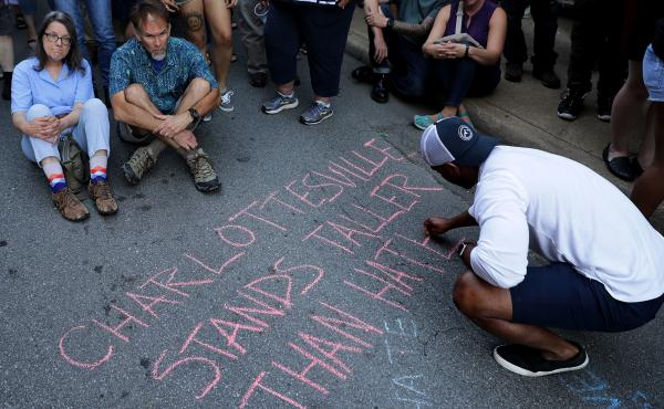 """Hundreds of people gather for a vigil on the spot where 32-year-old Heather Heyer was killed when a car plowed into a crowd of people protesting against the white supremacist """"Unite the Right"""" rally in Charlottesville, Va."""