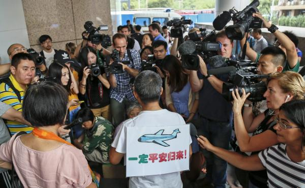"Surrounded by journalists, a relative of passengers of Malaysia Airlines Flight 370 wears a sign reading ""Must return safely!"" during a protest held by victims' families Thursday outside the Malaysia Airlines office in Beijing."
